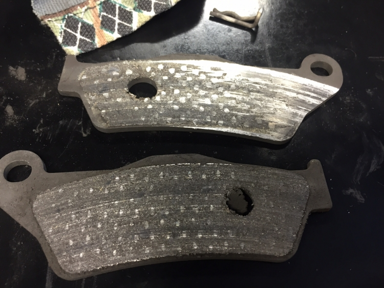 customer's brake pads that have been worn down to bare metal at Oz-racing's workshop
